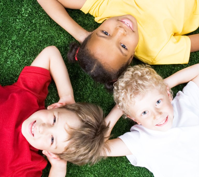Children laying on the grass. Preschool to Youth Education